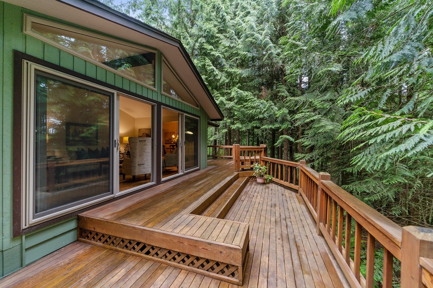A brown wooden deck surrounded by trees
