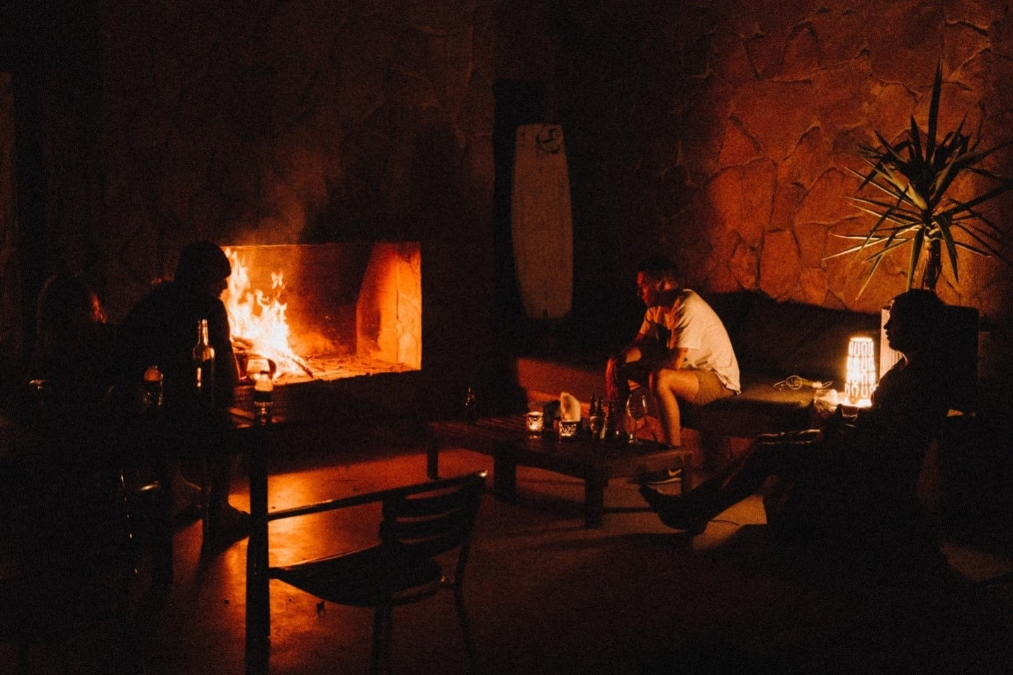 3 people sitting in a living room around a hearth.